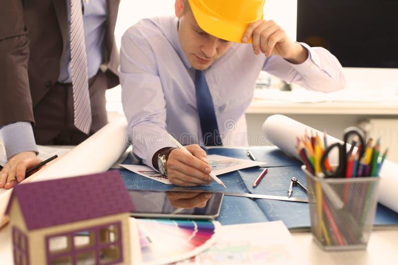 Un architetto Discussing House Project di due ingegneri immagine stock