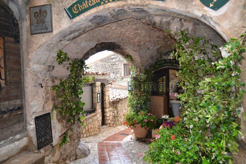 un arco con las flores en un pueblo francés imagen de archivo libre de regalías