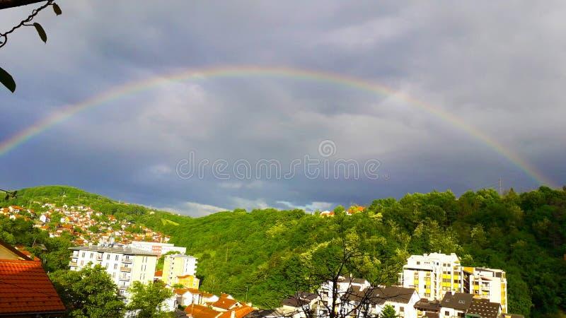 Un arco iris, fenómeno natural sobre la ciudad de Uzice foto de archivo