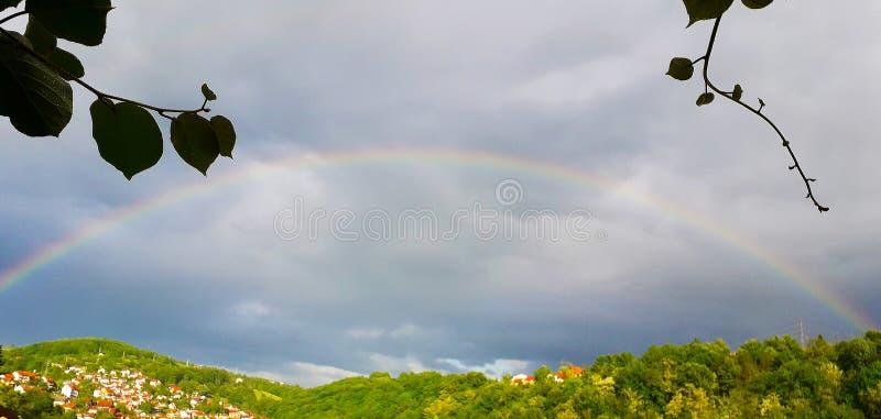Un arco iris, fenómeno natural sobre la ciudad de Uzice fotografía de archivo