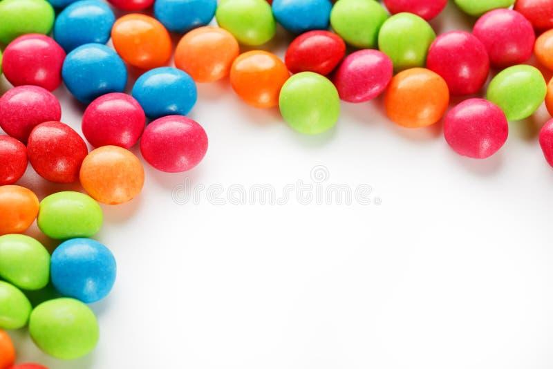 Un arcobaleno di colore dal primo piano multicolore delle caramelle, di confetto colorato multi della glassa su un fondo bianco immagini stock