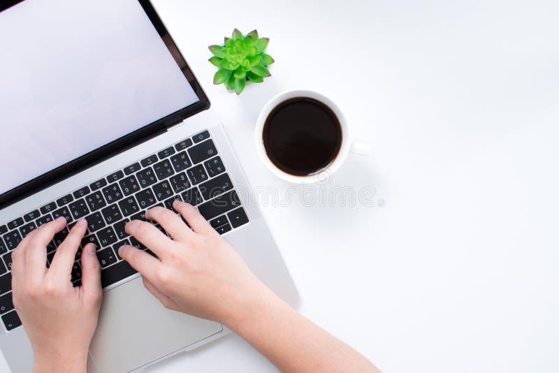 Un'area di lavoro con un computer portatile su una mano di una donna e della tavola semplice sta funzionando Con un'area della co fotografia stock libera da diritti
