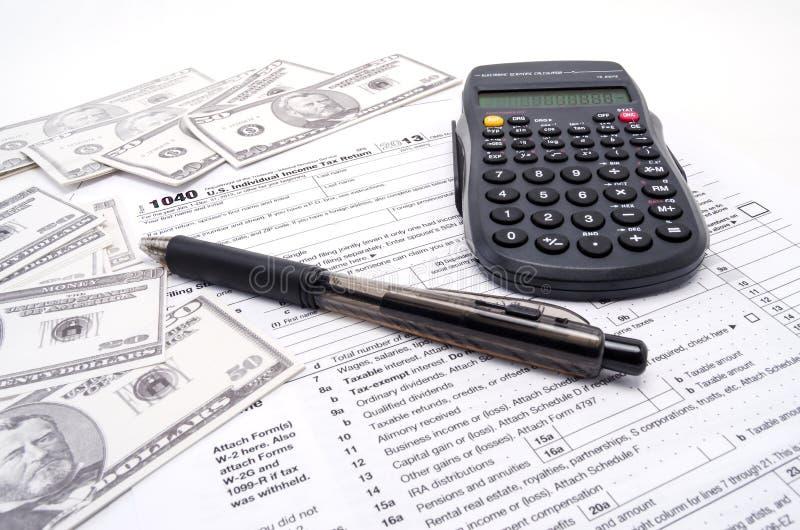 Un argent liquide et une calculatrice de feuille d'impôt  image stock