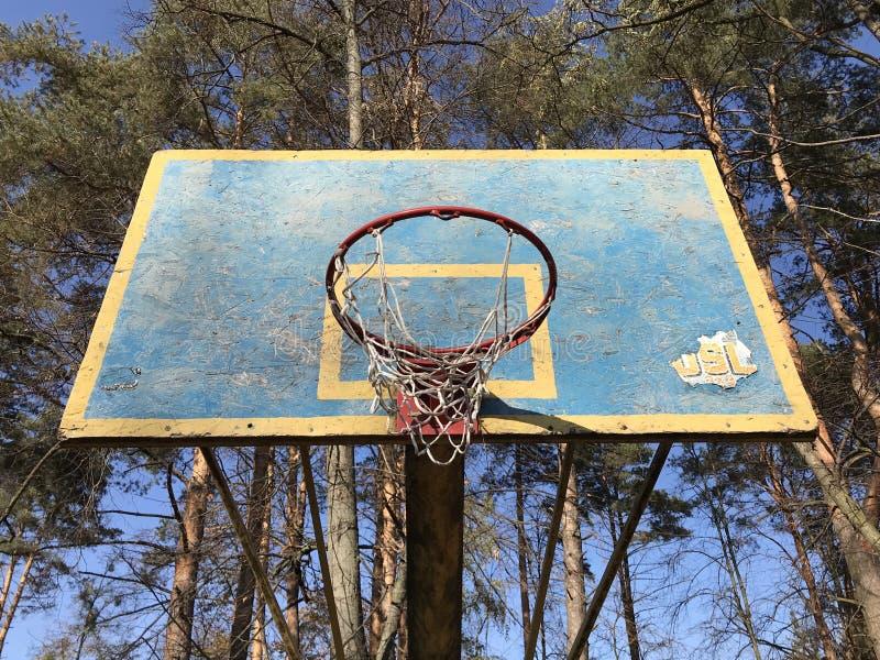 Un aro de baloncesto de la escuela vieja en el sol fotografía de archivo