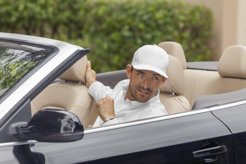 Un arrangement d'homme dans sa voiture convertible regarde plus de quelque chose ou quelqu'un hors du cadre images stock