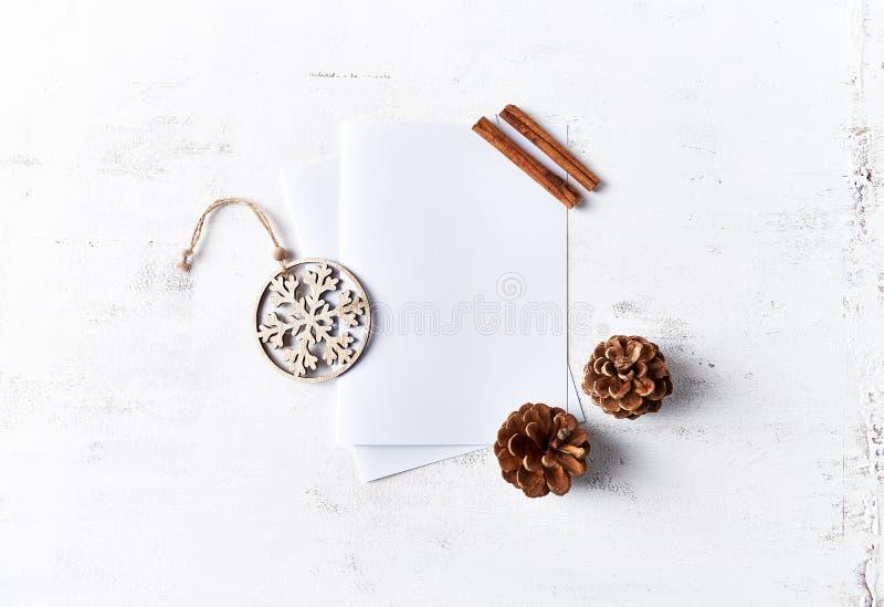 Un arreglo de las decoraciones de la Navidad y de las tarjetas de papel en blanco en el fondo de madera blanco flatlay Copie el e imagen de archivo libre de regalías