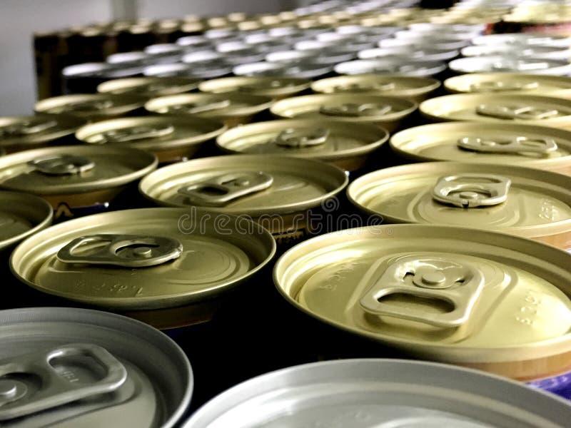 Un arsenal de latas de bebidas del café se centra en las tapas imagen de archivo libre de regalías