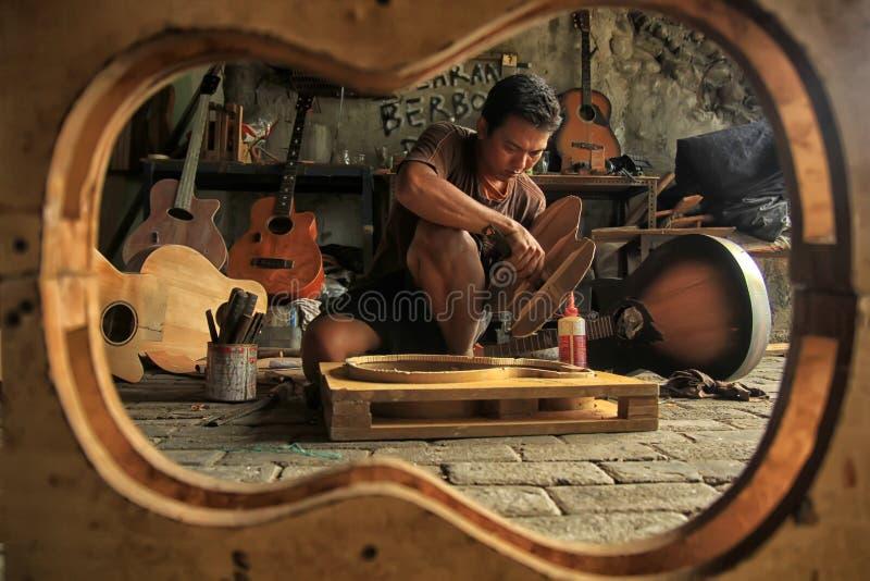 Un artesano de la guitarra está ocupado el hacer de órdenes de sus clientes imagenes de archivo