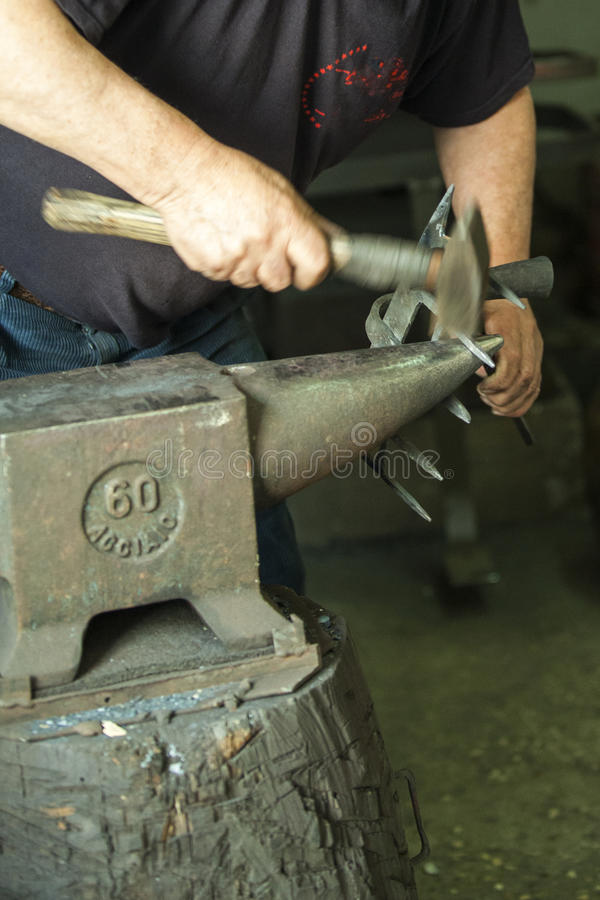 Download Un Artigiano Che Lavora Con Un Martello E Un'incudine Fotografia Stock - Immagine di forgia, ferro: 56886678