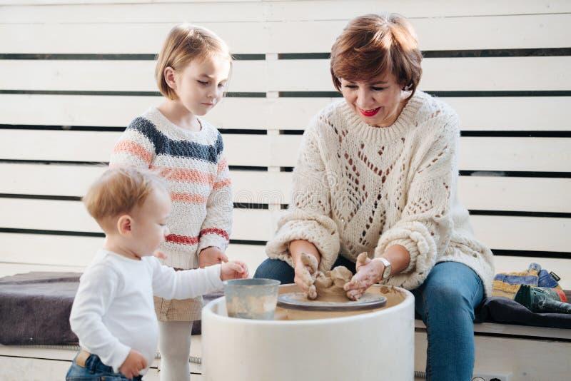 Un artisan de potier montre à une petite fille comment travailler avec la roue d'argile et de poterie Observation de frère images stock