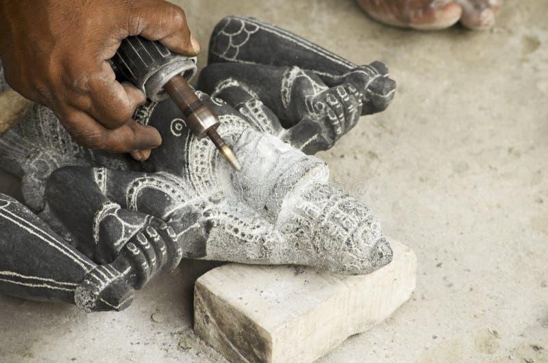 Un artista che dà i tocchi finali ad un idolo a Mahabalipuram, Tamil Nadu, India, Asia fotografie stock