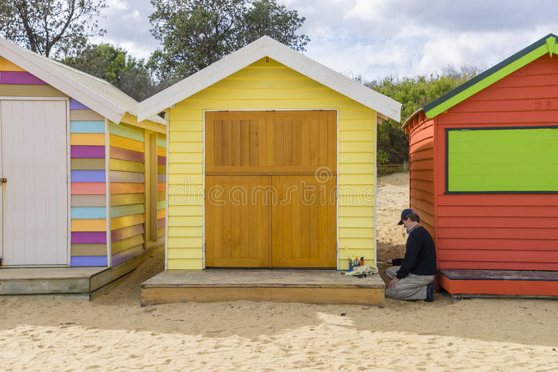 Un artista che dipinge una casa di bagno alla spiaggia della via di Dendy, Brighton a Melbourne immagine stock