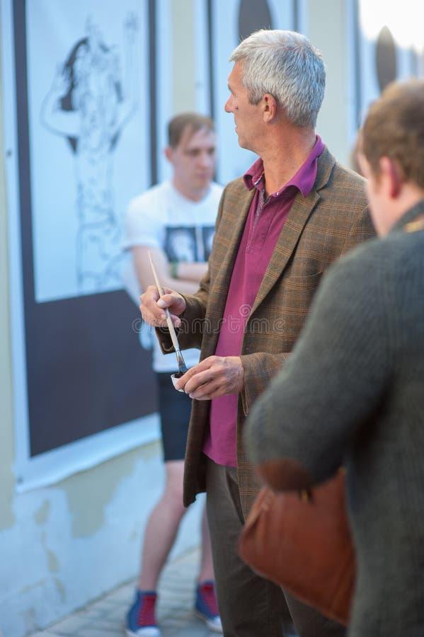 Un artista con una spazzola esamina il lavoro, una mostra pubblica degli impianti dagli artisti immagine stock