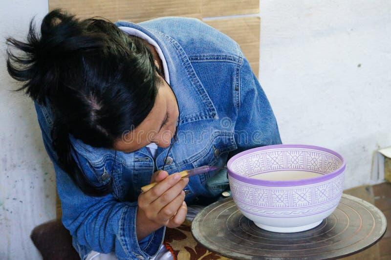 Un artista de cerámica pinta un diseño en un cuenco en Fes, Marruecos. fotografía de archivo libre de regalías