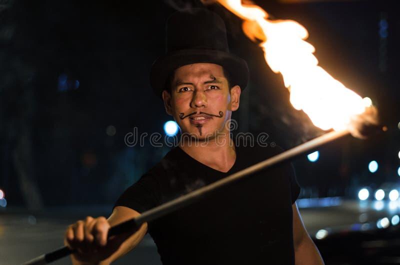 Un artista de la calle que hace una demostración en Lima - Perú, haciendo juegos malabares un palillo con el fuego en las parad imágenes de archivo libres de regalías