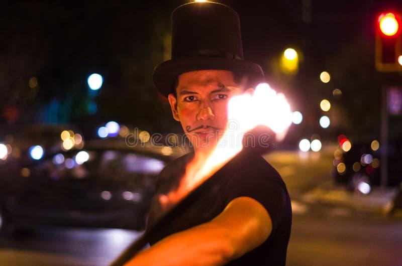 Un artista de la calle que hace una demostración en Lima - Perú, haciendo juegos malabares un palillo con el fuego en las parad foto de archivo