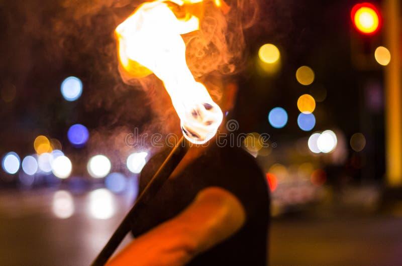 Un artista de la calle que hace una demostración en Lima - Perú, haciendo juegos malabares un palillo con el fuego en las parad fotos de archivo libres de regalías