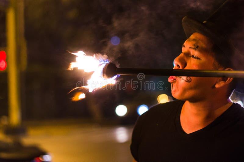 Un artista de la calle que hace una demostración en Lima - Perú, haciendo juegos malabares un palillo con el fuego en las parad fotos de archivo