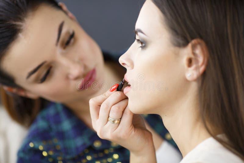 Un artista de maquillaje está aplicando maquillaje a una chica joven imagen de archivo