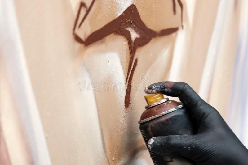 Un artista della via in guanti neri disegna un'immagine astratta facendo uso di una pittura di spruzzo marrone Concetto dei graff fotografia stock