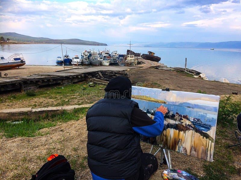 Un artista dipinge le barche immagini stock