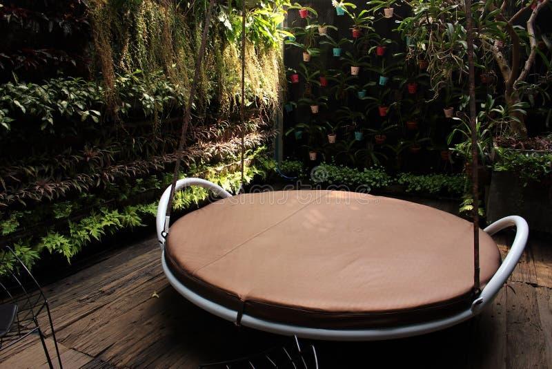 Un asiento grande del oscilación en un jardín tropical emparedado imagen de archivo libre de regalías