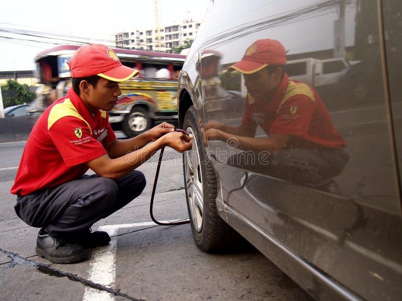 Un asistente de la estación de gasolina comprueba la presión de neumáticos del coche de un cliente foto de archivo libre de regalías
