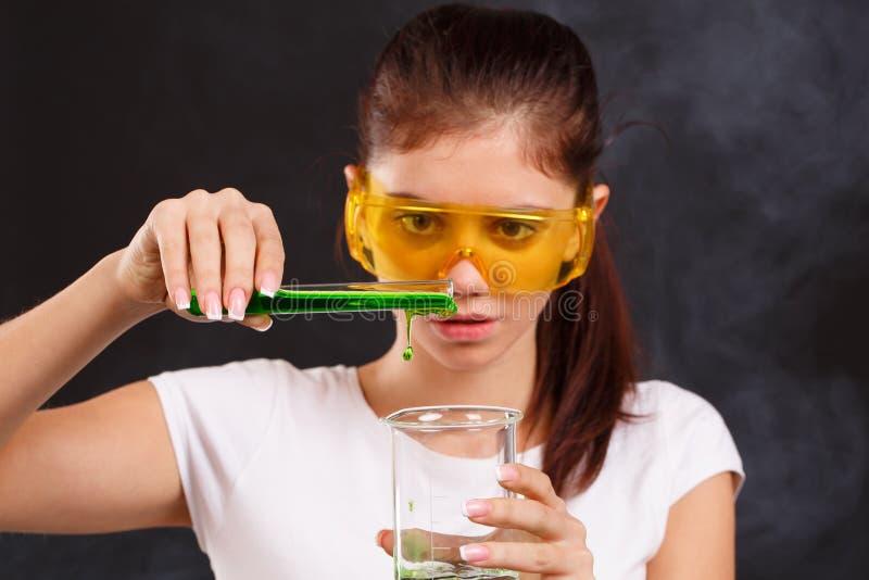 Un assistant de laboratoire de fille verse le liquide dans un tube à essai dans un plan rapproché de flacon sur un fond noir image libre de droits
