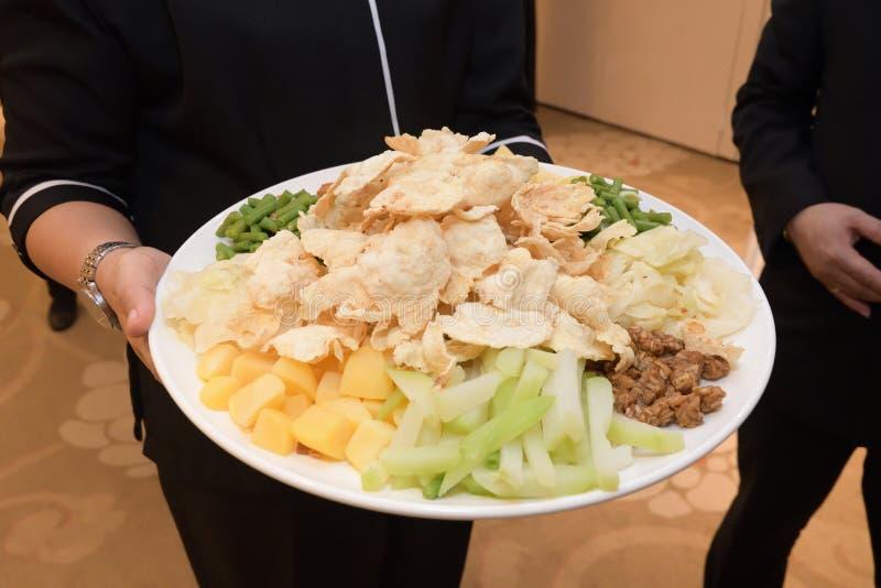 Un assortiment de plats végétariens de délices sur un plateau tenu entre les mains photo libre de droits