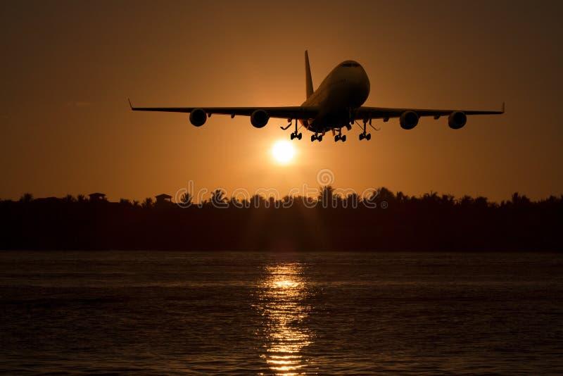 Un aterrizaje de aeroplano comercial/sacar en la puesta del sol stock de ilustración