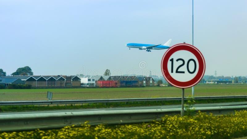 Un aterrizaje de aeroplano sobre edificios en un día con un limitador de la velocidad de un camino fotografía de archivo