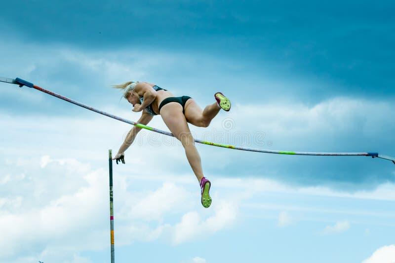 Un athlète féminin concurrençant dans la chambre forte de poteau photos libres de droits