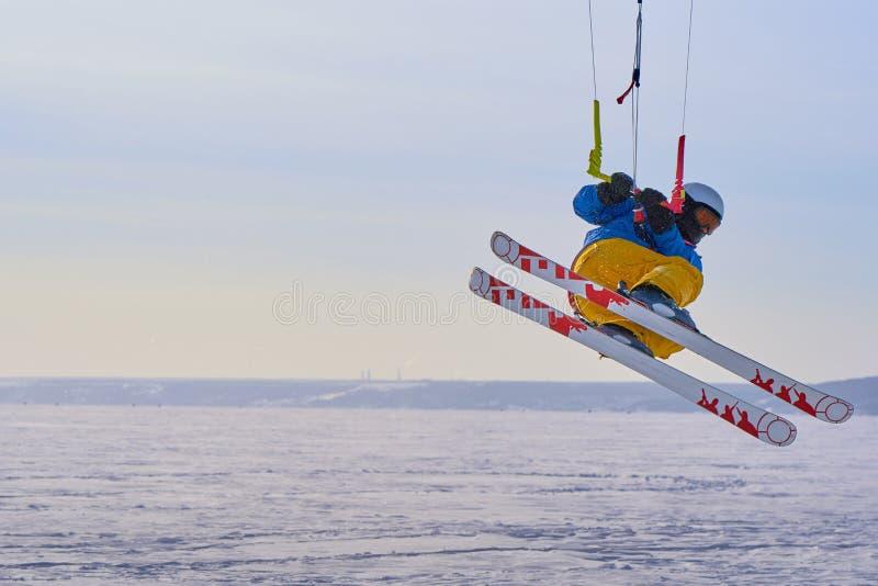 Un athlète masculin s'est engagé dans la neige kiting sur la glace d'un grand lac neigeux Il exécute le saut Jour givré ensoleill photos libres de droits