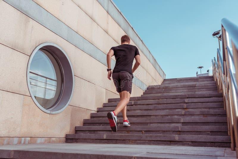 Un athlète masculin, vue de derrière, court le matin sur un escalier, en été en ville Les shorts de T-shirt Sportswear photographie stock