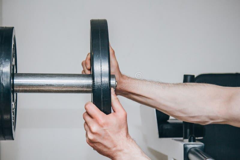 Un athl?te avec de grandes mains ajoute le poids par les disques en m?tal ? l'appareil s'exer?ant au centre de formation mat?riel images libres de droits