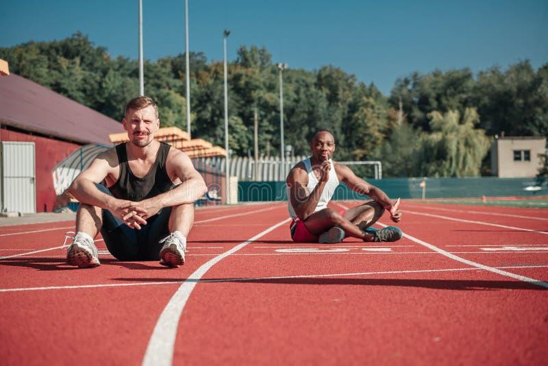 Un atleta blanco y un hombre negro con una piruleta se sientan en el estadio foto de archivo