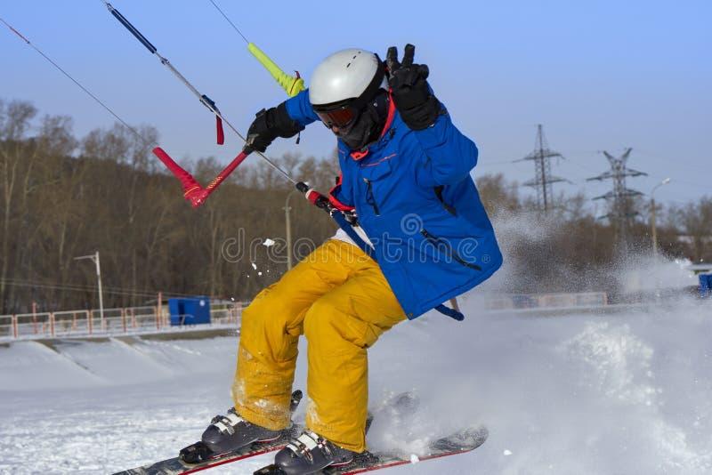 Un atleta de sexo masculino enganchó a la nieve kiting en el hielo de un lago nevoso grande Él realiza el salto Día escarchado so imágenes de archivo libres de regalías
