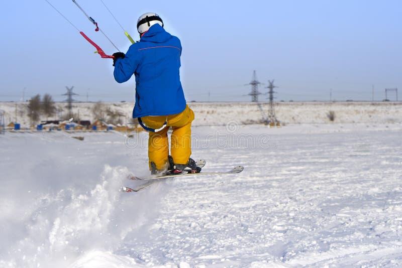 Un atleta de sexo masculino enganchó a la nieve kiting en el hielo de un lago nevoso grande Él realiza el salto Día escarchado so imagenes de archivo