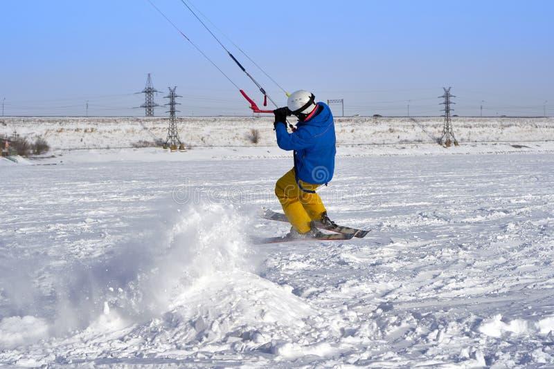 Un atleta de sexo masculino enganchó a la nieve kiting en el hielo de un lago nevoso grande Él realiza el salto Día escarchado so fotografía de archivo