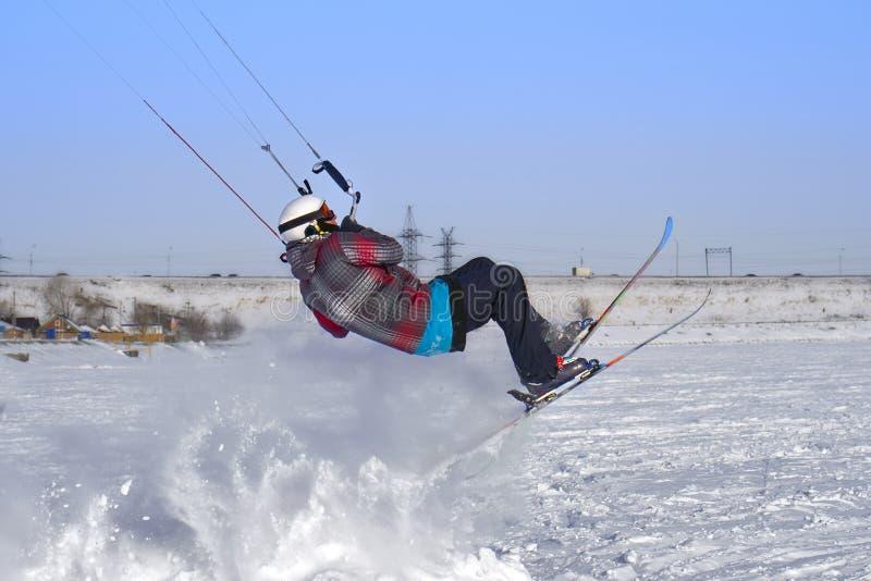 Un atleta de sexo masculino enganchó a la nieve kiting en el hielo de un lago nevoso grande Él realiza el salto Día escarchado so foto de archivo libre de regalías