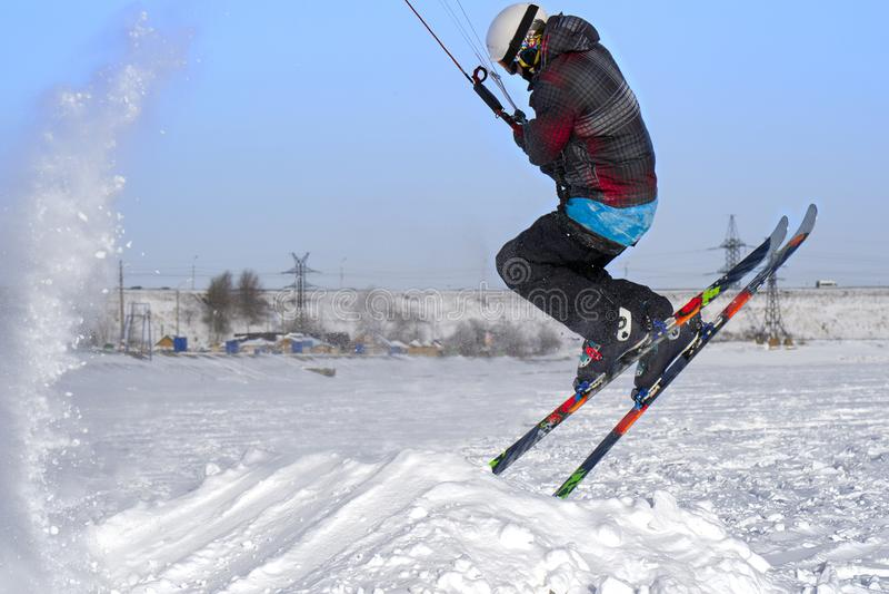 Un atleta de sexo masculino enganchó a la nieve kiting en el hielo de un lago nevoso grande Él realiza el salto Día escarchado so fotos de archivo libres de regalías