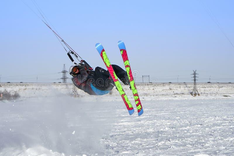Un atleta de sexo masculino enganchó a la nieve kiting en el hielo de un lago nevoso grande Él realiza el salto Día escarchado so imagen de archivo