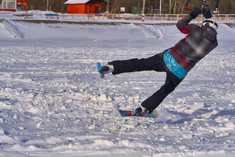 Un atleta de sexo masculino enganchó a la nieve kiting en el hielo de un lago nevoso grande Él realiza el salto Día escarchado so fotografía de archivo libre de regalías