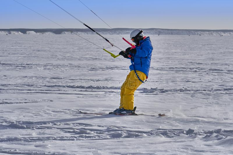 Un atleta de sexo masculino enganchó a la nieve kiting en el hielo de un lago nevoso grande Él va a esquiar en la nieve imágenes de archivo libres de regalías