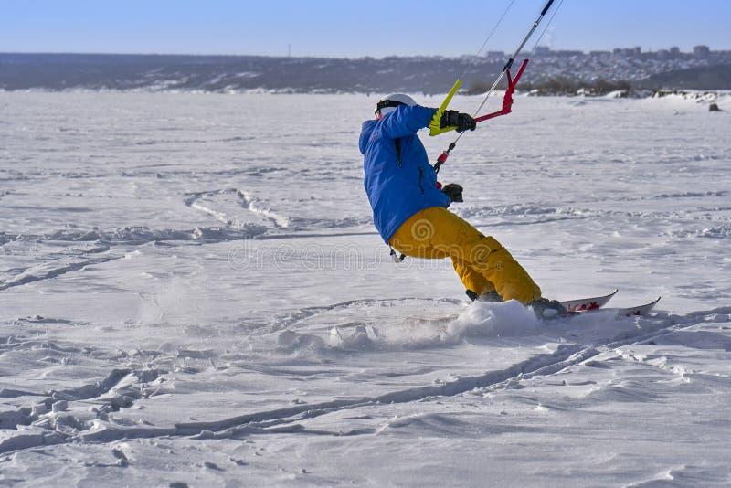 Un atleta de sexo masculino enganchó a la nieve kiting en el hielo de un lago nevoso grande Él va a esquiar en la nieve imagen de archivo