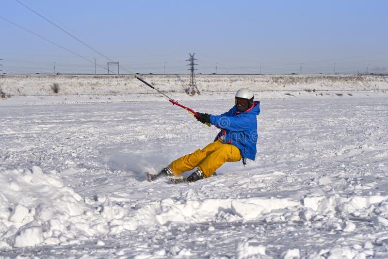 Un atleta de sexo masculino enganchó a la nieve kiting en el hielo de un lago nevoso grande Él va a esquiar en la nieve fotos de archivo libres de regalías