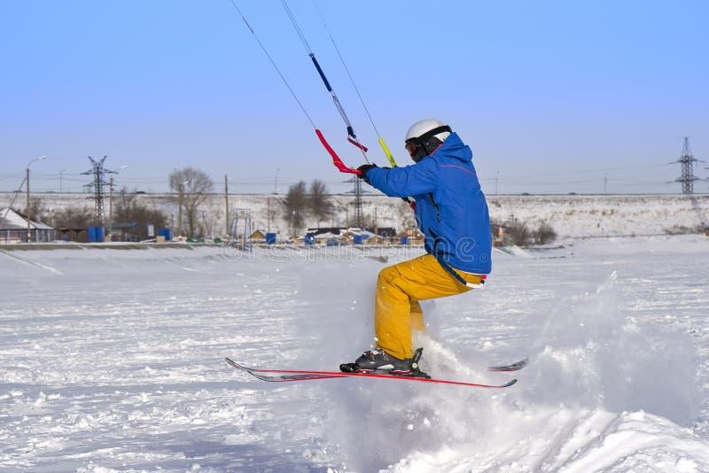 Un atleta de sexo masculino enganchó a la nieve kiting en el hielo de un lago nevoso grande Él va a esquiar en la nieve fotografía de archivo