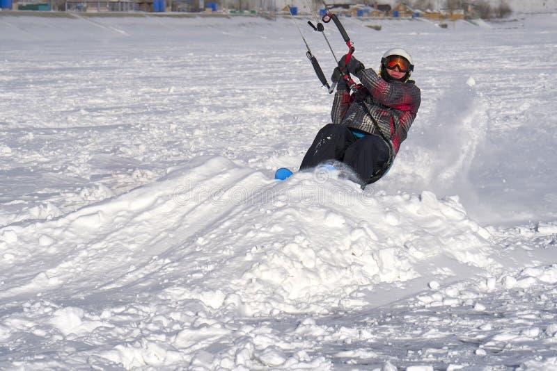 Un atleta de sexo masculino enganchó a la nieve kiting en el hielo de un lago nevoso grande Él va a esquiar en la nieve imagenes de archivo