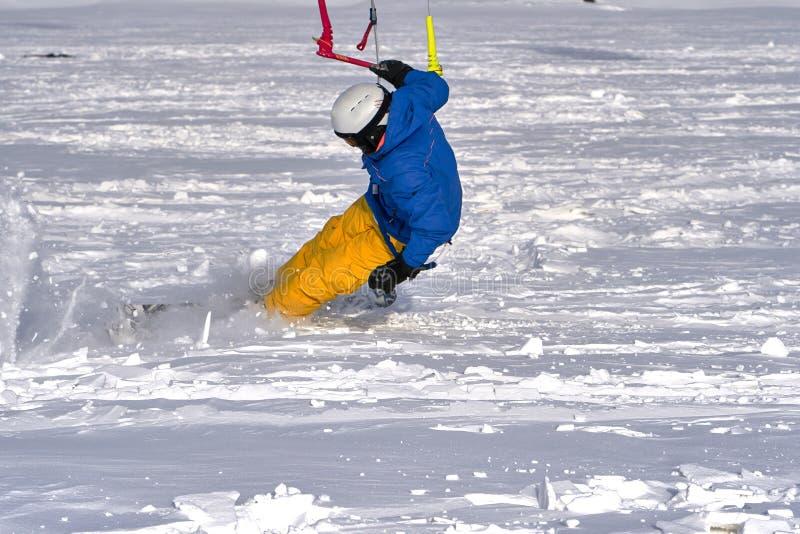 Un atleta de sexo masculino enganchó a la nieve kiting en el hielo de un lago nevoso grande Él va a esquiar en la nieve fotografía de archivo libre de regalías