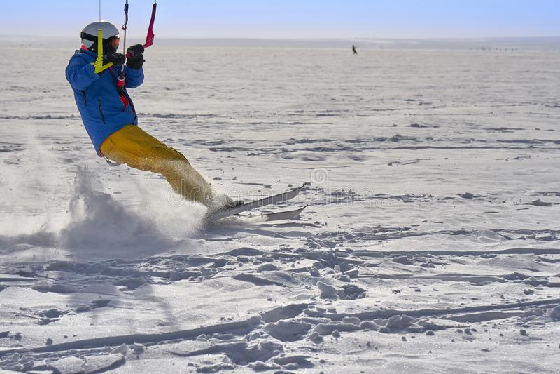 Un atleta de sexo masculino enganchó a la nieve kiting en el hielo de un lago nevoso grande Él va a esquiar en la nieve foto de archivo libre de regalías